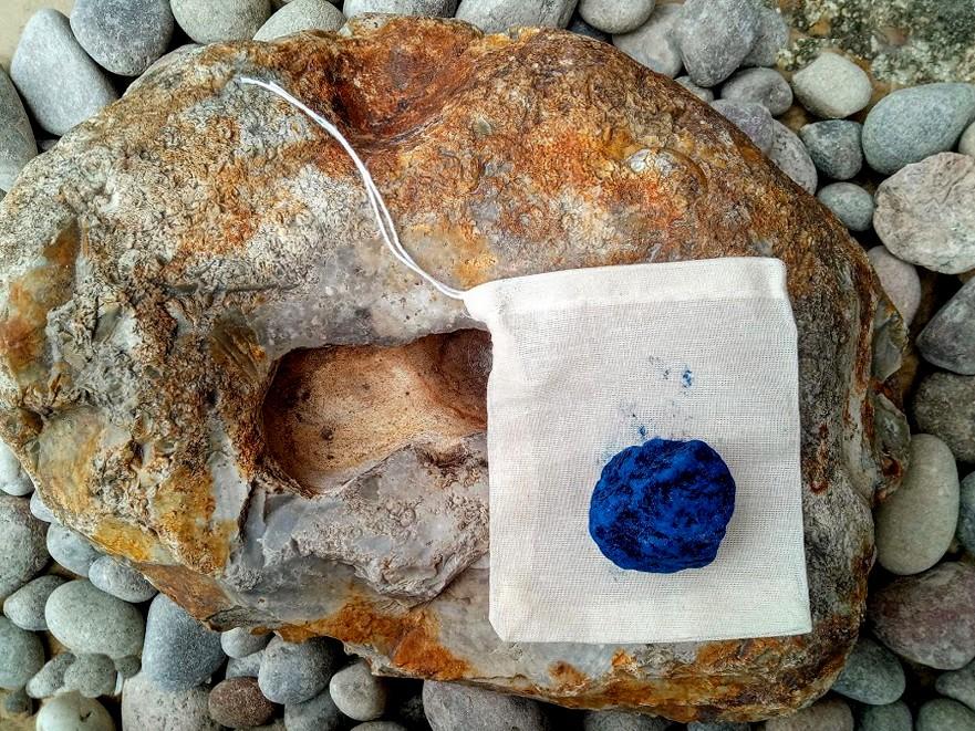 natural blue indigo block with cotton drawstring bag on rocks